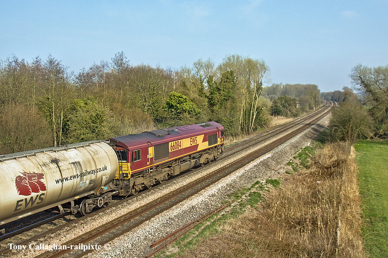25th Mar 11:  Heading away from Theale and running through Burghfield is 66084 working 6E44 to take the oil empties back to Lindsey