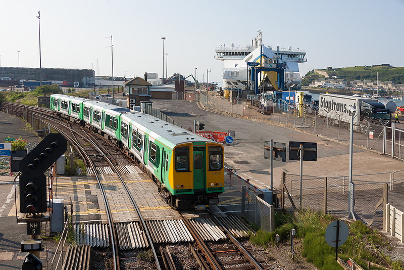 10th Aug  12:  As Continental trucks roll off the 'Seven Sisters' ferry the 08.58 from Seaford in the hands of 313220 rounds the curve into Newhaven Harbour.