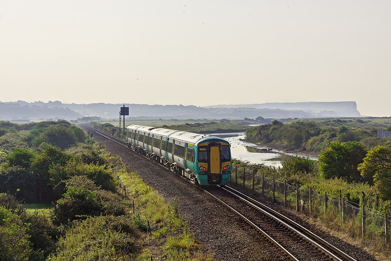 10th Aug 12:  With Seaford Head in the distance 377451 working a Brighton to Seaford service heads into the misty morning light as it leaves Newhaven