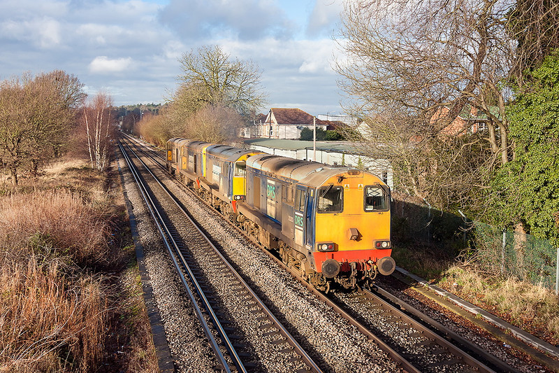 21st Dec 12:    4 DRS Class  20 locos # 20303/304/302/301 are being moved to Eastleigh from Willesden to be stored.   Still filthy after RHTT duties 0Z36 is pictured crossing Chertsey Meads in a welcome patch of sunlight