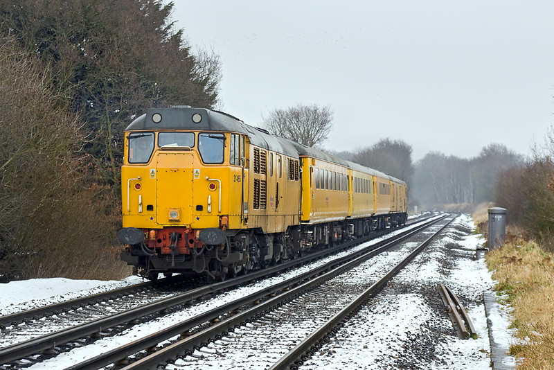 6th Feb 12:  Although it is up hill the ED is doing all the work as 1Q84 with 31465 on the tail passes Waterloo Road level crossing in Wokingham