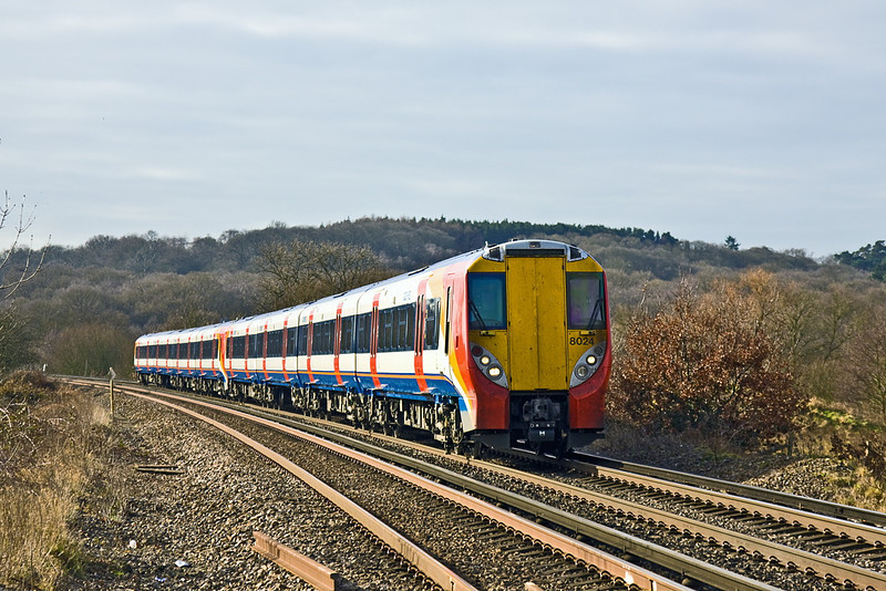 21st Feb 12:  Nearing Rusham Level Crossing are 458024 with 458010 forming the 09.42 (2C26) from Reading to Waterloo.  The sunshine was not to last