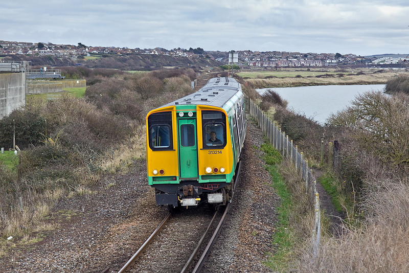 10th Jan 12:  Just starting the final curve into Newhaven Harbour Station is <br /> 313214 forming the 14.58 from Seaford to Brighton.  The stretch of water is the remains of the River Ouse that was cut off when Newhaven Harbour was reconstructed to give a better exit to the sea.