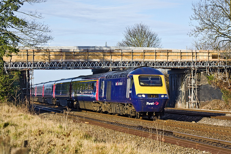 6th Jan 12:  43028 races under the new bridge works at Lower Basildon working 1L51   the 10.55 from Cardiff.  A temporary foot bridge in front of the new concrete road bridge carries cables and gave workers access across the lines when the old bridge was removed over Christmas