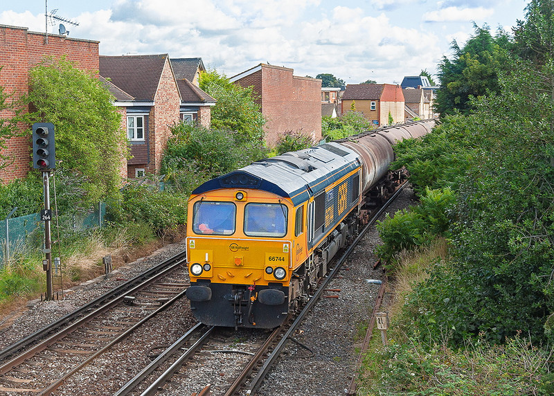 30th Jul 12:  66744 'Crossrail' charges through Egham on the point of 6O34 empty tanks from Parkstone Quay to the Carless Oil terminal at Holybourne near Alton.  Most of the tanks passed in full sun !!  This loco was originally DRS 66409 and then Colas 66843.