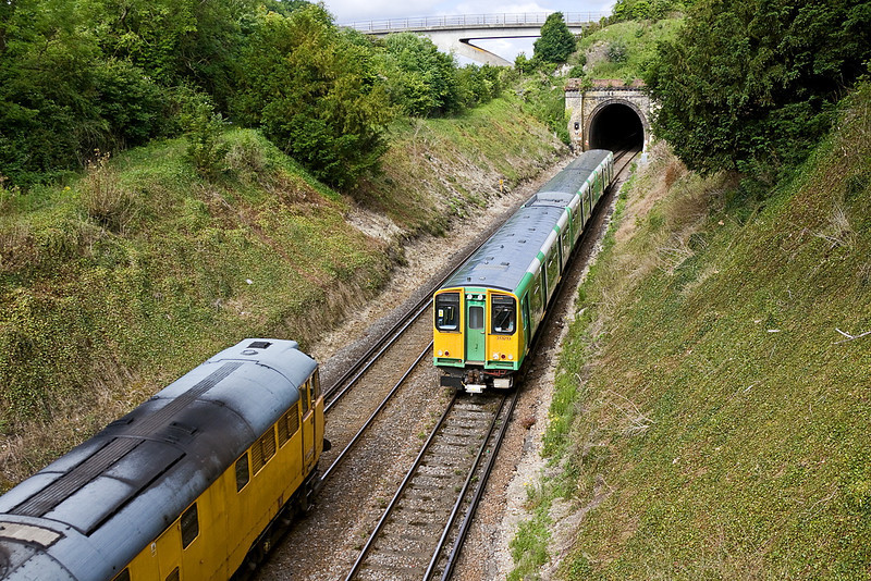 7th Jul 12:  313213 forming the 09.13 Brighton to Seaford (2F49) is about to mess my shot of 31233 working 1Q14 to Brighton as it leaves Lewes