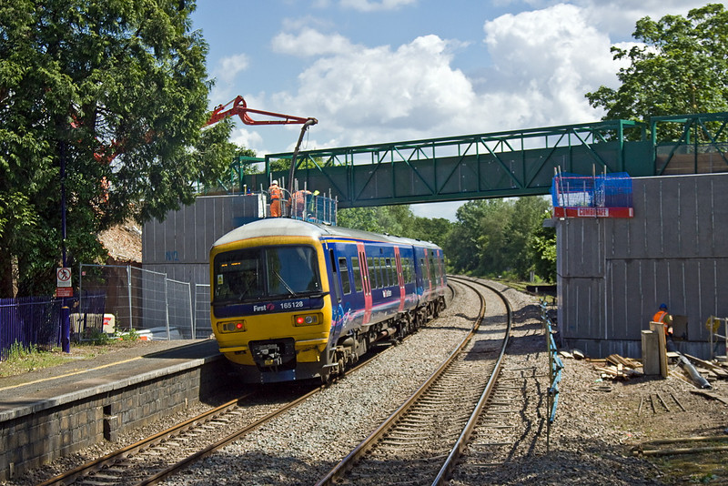 13th Jun 12:  165128 leaves Aldermaston for Reading.  The new abutments are nearly ready to receive the new A340 road bridge.  The concrete will eventually be covered in brick work.