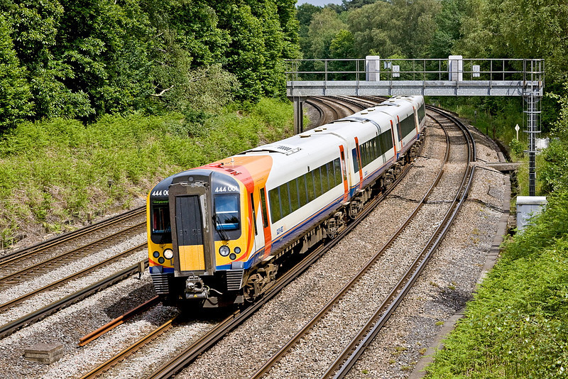 20th Jun 12:   Class pioneer 444001 rounds the curve through Pirbright with a Weymouth service