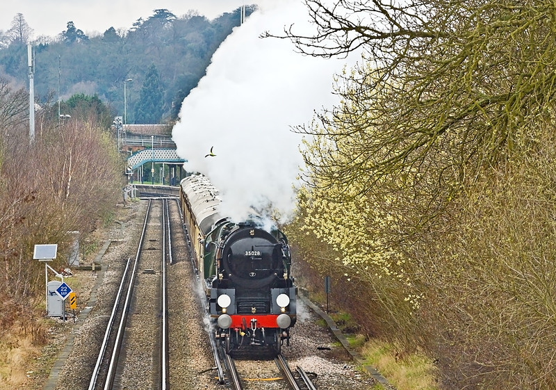 """17th Mar 12:  Accelerating hard away from Chertsey is 35028 """"Clan Line"""" heading the VSOE 'Surrey Hills Luncheon Special'.  A pigeon is racing to keep out of the way."""