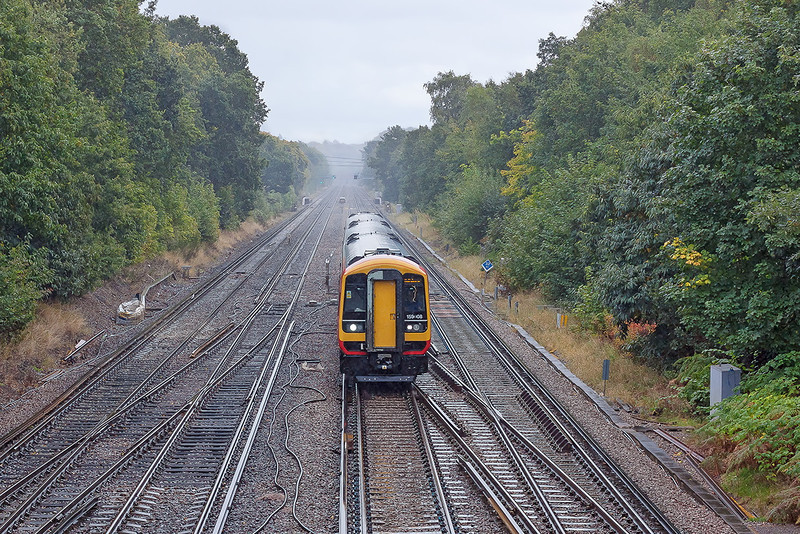 2nd Oct 12:  In steady rain 1L35 ,formed of 159008, is on time as it reaches Farnborough.  The 12.50 from Waterloo is heading for Salisbury