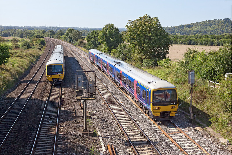 5th Sep 12:  166216 potters along the Relief Line at Purley on Thames while working 2P60 the 14.37 Oxford to Paddington as 166210 on an ECS overtakes