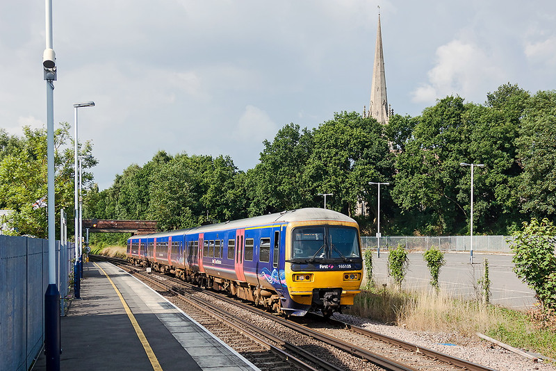 25th Aug 13:  With the spire of St Pauls church dominating the skyline 165105 arrives at Wokingham with 1O80 the 15.18 from Reading to Gatwick
