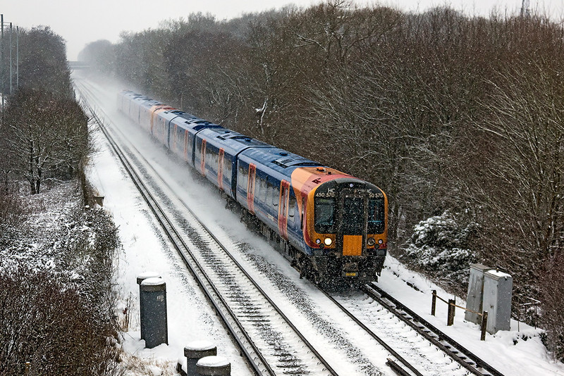 20th Jan 13;  Kicking up the snow are 450570+450550 working 2C42 from Reading to Weybridge as they near Bracknell.    This train will also call at Chertsey and Addlestone, the revised service being caused by an engineering blockade on the Staines route.  This required that the Weybridge to Waterloo service was cancelled.