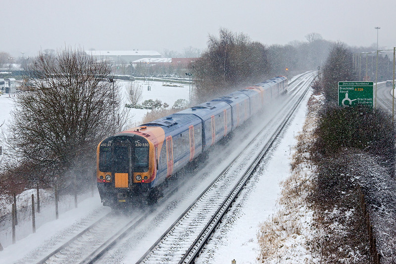 20th Jan 13;  Kicking up the snow are 450550+450570 working 2C42 from Reading to Weybridge as they near Bracknell.    This train will also call at Chertsey and Addlestone, the revised service being caused by an engineering blockade on the Staines route.  This required that the Weybridge to Waterloo service was cancelled.