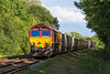 7th Aug 14:  In dappled shade 66009 hurries towards Sherrington Lane  crossing bringing  the empties from Woking to Merehead