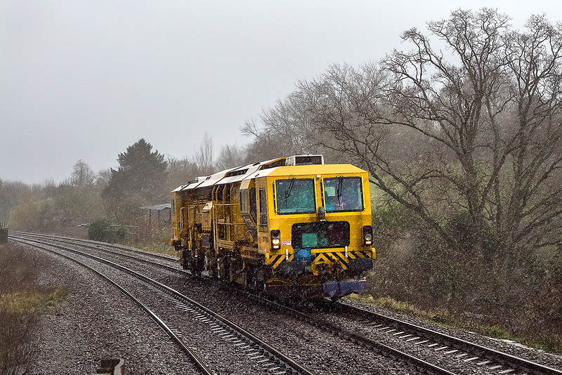 6th Jan 14:  In torrential rain a unidentified Tamper drifts down hill through Dilton Marsh while heading to Fairwater Yard from Andover