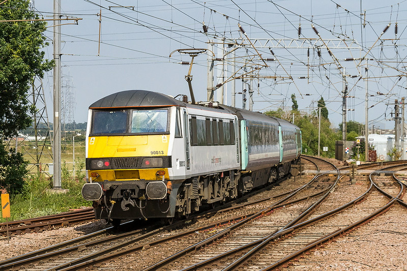16th Jul 14:  It is 14.36 and 90013 is sbout to cross the level crossing as it departs from Manningtree with the 14.30 to Norwich from Liverpool Street