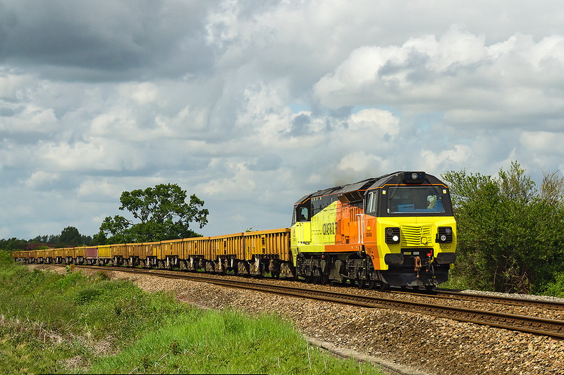 25th May 14 Colas Freight 70807 brings a rake oj JNS and MLA wagons from Gaer Junction to Westbury though North Bradley in a very fortunarte patch of Sun