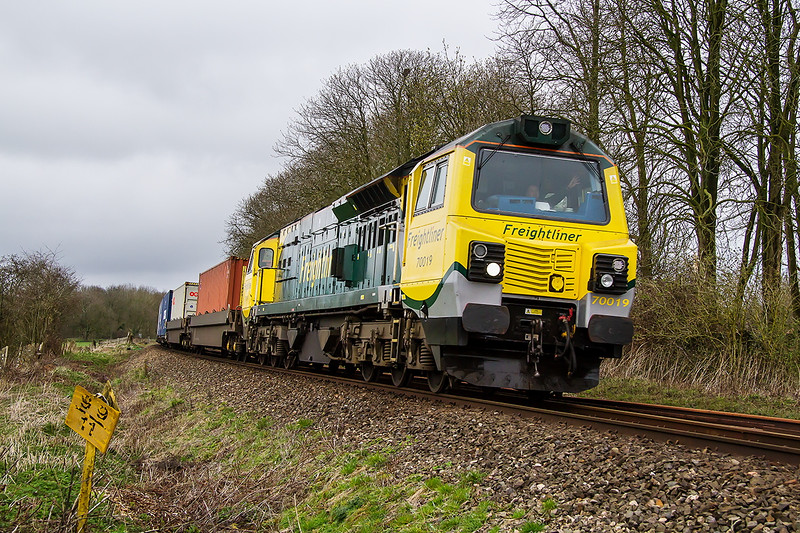 3rd Apr 2015:  With the driver giving a good wave 70019  leans to the curve on the northern edge of Melksham with 4O51 from Wentloog to Southampton Maritime.  With the line through Reading closed for Easter engineering work this train has to be  diverted via Westbury  neccessitating a reversal at Swindon