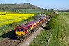 23rd Apr 2015:  With  Arn Hll in the distance and the Rape Seed in full bloom 66047 & 66150 bring 6V41, with 5 wagons of used track parts,  back to Westbury from Eastlleigh.  Pictured from the bridge on the Warminster bypass