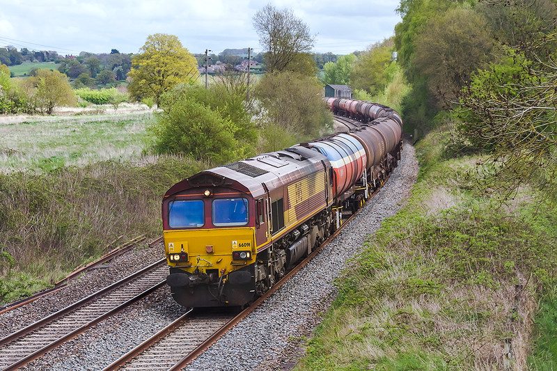 25th Apr 2015:  6B33 the diverted via the B & H Theale to Margam empty Murco tanks is in the hands of 66091 as it runs down hill away from the site of Lavington Station
