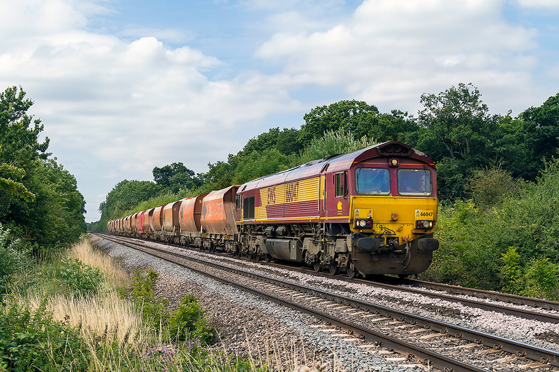 12th Aug 2015:  66047 is at Masters Crossing in Fairwood  with the usual rusty looking rake forming 6M20 for St Pancrass Churchyard Sidings from Whatley Quarry