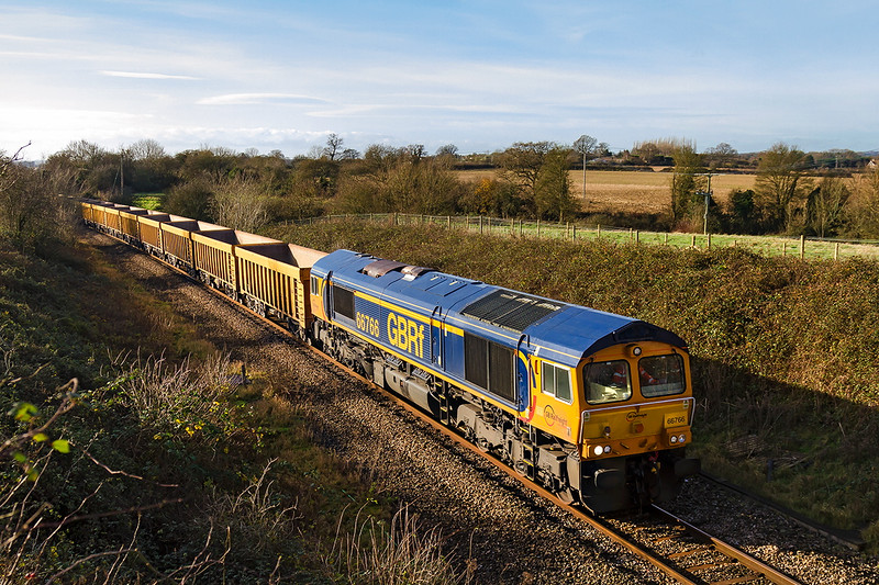 9th Dec 2015:  Captured as it passes through Broughton Gifford on the single line between Trowbridge and Chippenham via Melksham is 66766.  6M40 is the regular service to take wagons to Stud Farm in Leicestershire to  be refilled with ballast and returned to Westbury where it will be used to replennish the Virtual Quarry