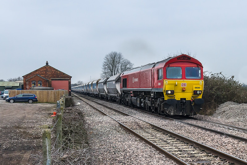 12th Feb 2015:  Making a healthy noise 59203 with a load of 44 wagons passes the old Goods Shed at the site of Edington and Bratton station.  6L21 is working from Whatley Quarry to Dagenham