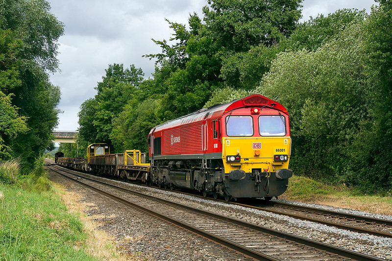 6th  Jul 2015:  66001 runns through Wylye with the morning departmental from Westbury to Eastleigh.  The location is Townsend Crossing on the northern outskirts of the village. The modern bridge in the background carries the A303