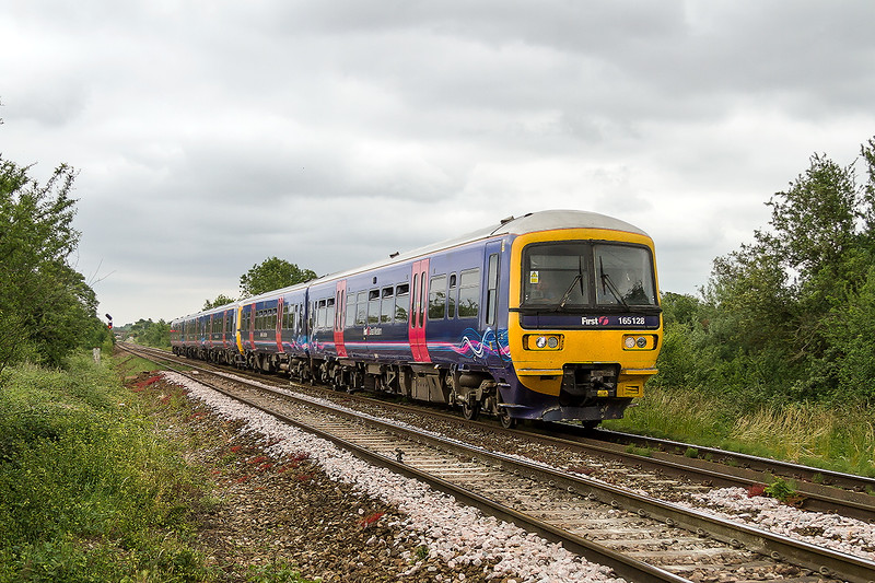 26th Jun 2015:   With the days of loco hauled extras to the Glastonbury Festival long gone the only excitement now, well not really very exciting, is the appearance of London Suburban units.  165125 and 166214 are captured at Masters Crossing in Fairwood when working 1Z32 from Paddington to Castle Cary