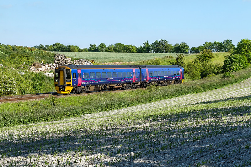 10th Jun 2015:  Th 17.28 from Warminster to Worcester Shrub Hill,2E27, in the hands of 158763 runs down the grade away from Upton Scudamore.  In a couple of months this shot, from the edge of ther field, will no longer be possible  due to the height of the Maize crop.