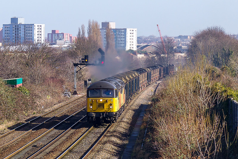 "10th Mar2015:   ""Here it comes !!'    Running about an hour early past the site of Malago Vale Carriage Sidings in Bristol is 6V54 the empty log carriers from Chirk to Teigngrace.  Going well and making a nice nice roar are Colas Grids 56105 & 56078"