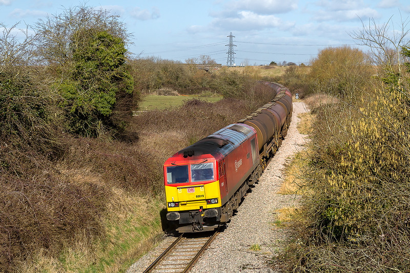 10th Mar 2015:  Running through the village of Westerleigh on what was the old Midlend main line to Bristol is 60019  with 6B13 the 05.00 loaded Murco tanks from Roberston to Westerleigh.Visible in the distance is the bridge carrying the GW Main Line over the branch.