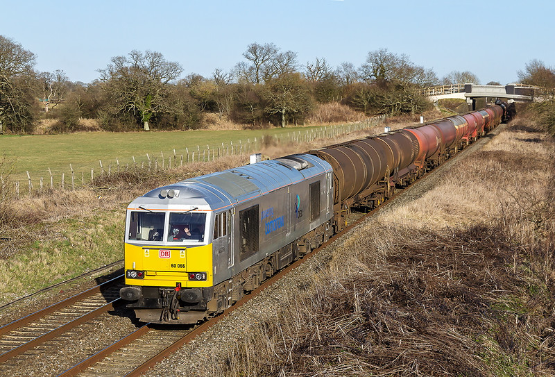 10th Mar 2015:  Recently restored to use 60066 in silver livery branded 'Powering Tomorrow'  'Drax' is heading 6B33 the empty Murco tanks from Theale to Robeston.  The location is Acton Turville