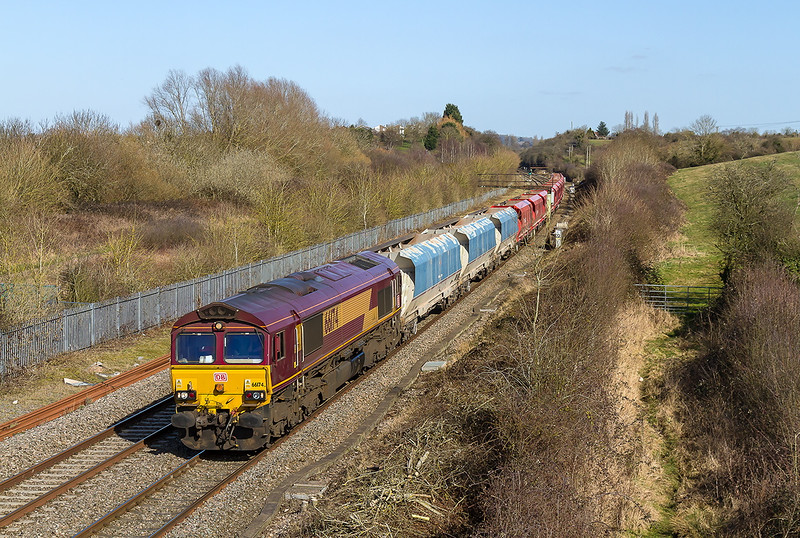 10th Mar 2015:  The site of Wapley sidings sees 66174 towing 3 old National Power and a good rake of Schenker red hoppers to Moreton on Lugg from  Hayes