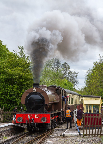 4th May 2015:  The fireman leans from the cab of Hunslet Austerity WBR No15 as it arrives at Bitton on the Avon Valley Railway to pass the section staff back to the signal man.