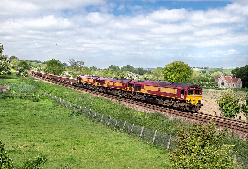 27th  May 2015:  With the sun dipping at just the wrong momentat Little Langford  66232 is the EWS branded filler in the DB Schenker sandwich of 66156 & 66014 as they head 6O41 departmental from Westburey to Eastleigh