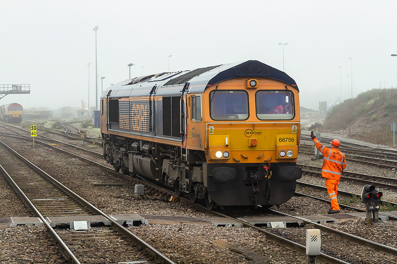 2nd Nov 2015:  On a foggy morning 66756 arrives at Westbury having worked 0V40 from Eastleigh.  It will later work 6M40 to Stud Farm.  The shunter is advising the driver of where  the waiting wagons are to be found