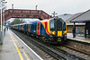 31st Jan 2016:  The  10.54 from Reading to Waterloo, 2C30,  formed of 450098 & 450087 arriving at Martins Heron station in Bracknell.  It looks that there are only two peopple waiting to board but there were about 20 more keeping dry packed into the Waiting room/booking hall  off to the right