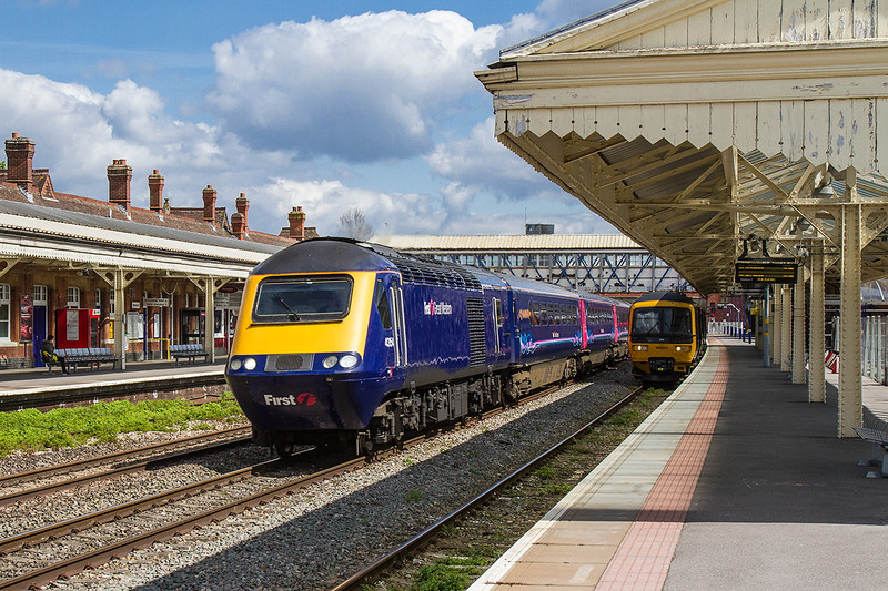 23rd Apr 2016:  Racing through Newbury is 43154 leading on 1B40 the12.30 Paddington to Swansea.  Resting in Platform 1 is GWR liveried 166204 'Norman Topsom MBE' with the 13.19 to Bedwyn.  The Up platform, Number 2, is actually still in use though weeds do seem to be gaining the upper hand