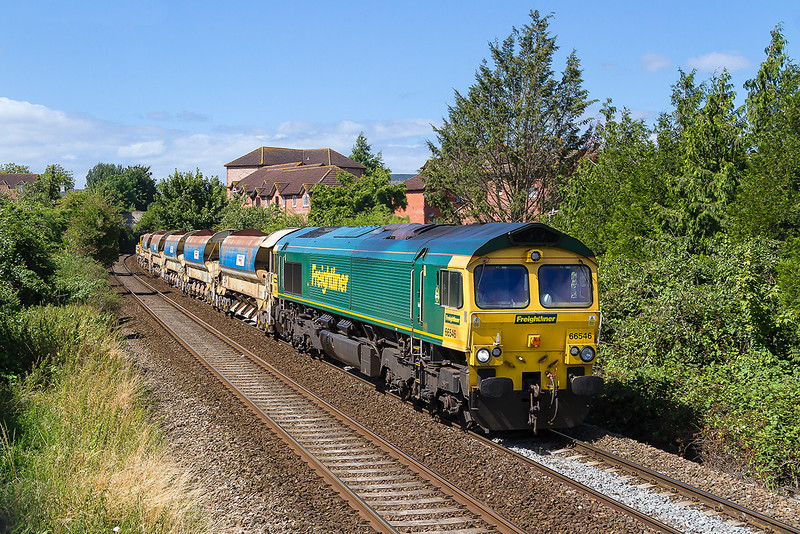 7th Aug 2016:  7Y59 is working from Maindee East Junction to Westbury and is seen as it leaves Trowbridge.  On the front of the Autoballasters a crane and some track pannels is 66546 with 66526 on the other end