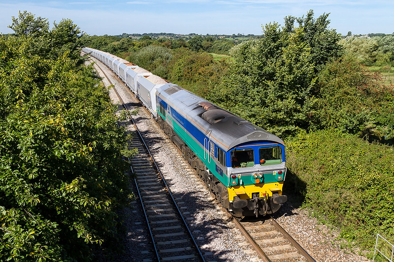 23rd Aug 2016:  The shot looking West at Fairwood Road is becoming rapidly overgrown.  Here 59002 is working 7A74 from Whatley to Theale  with 21 new HOA hoppers in tow