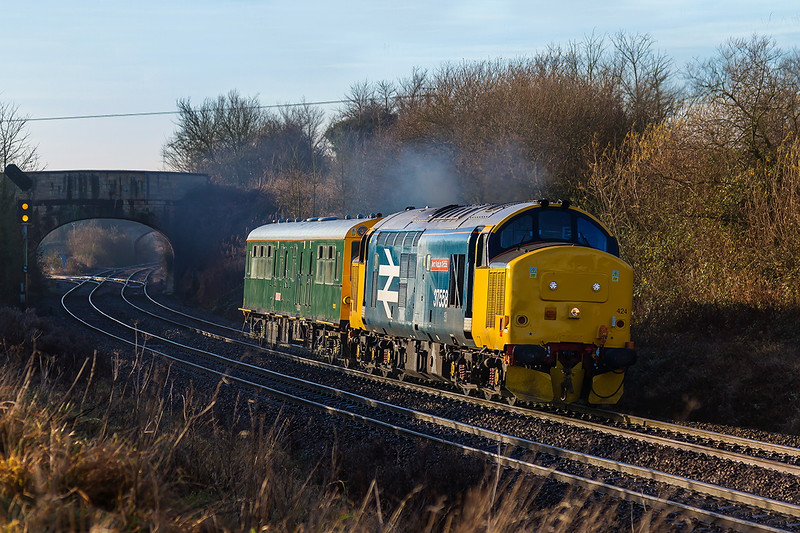 14th Dec 2016:  Having started from  Ealing Broadway and traversed the Berks & Hants line 2Z02 was booked to use the East Chord at Westbury to get onto the line to Trowbridge. Being pressed for time  and      knowing that it was being pushed the going away shot at Hawkeridge Junction was my only option.  To my surprse it reversed in the station so this is the best that I could  manage.  The loco is 37424 as shown on the front though now named 'Avro Vulcan XH388' it carries the number 37588 on the side.  The destination is Reading