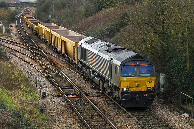 1st Feb 2016:  Still in Grey livery 66748 passes over Hawkeridge Junction while working 6M40 from Westbury to Stud Farm.  On what had been a dull and drizzly day the clouds suddenly began to thin making the very back lit picture difficult to Control
