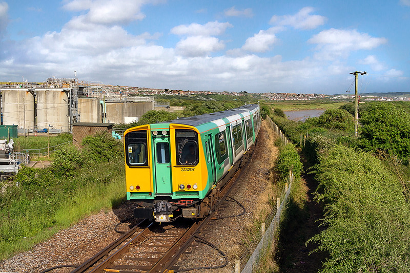 2nd Jul 2016:  2F80 ins the 07.25 from Seaford to Brighton is today allocated to 313207.  Pictured as it nears Newhaven Harbour station.  The patch of water  to the right of the rear of the train is the original course of the River Ouse that was cut off when the harbour was redeveloped