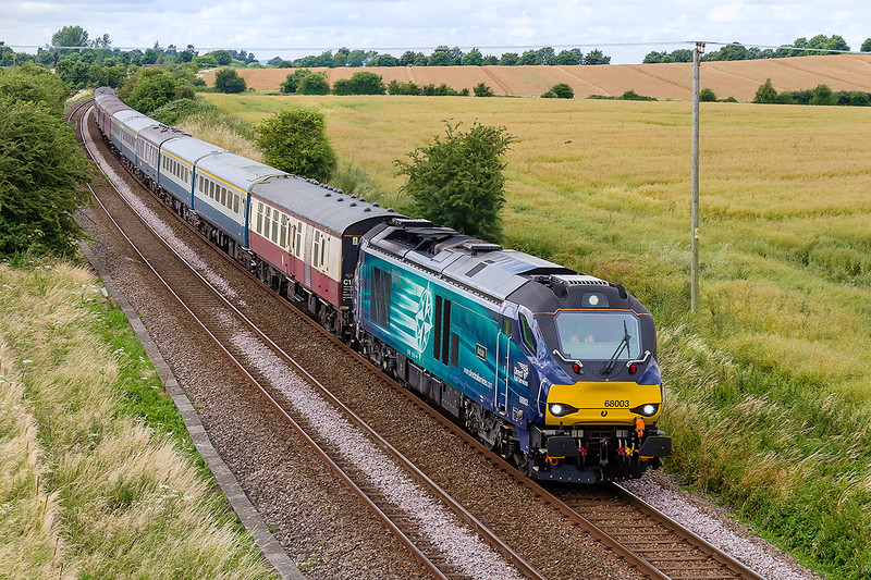 17tyh Jul 2016:  5Z72 the ECS move from Taunton Fairwater Yard to Eastleigh was originally routed via Castle Cary with a reversal at Westbury but it went via Bristol in stead.  Missing the sun of course 67003 'Astute' is captured from the Granada Bridge between Westbury and Warminster