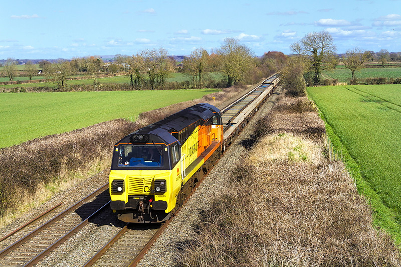 25th Mar 2016:  On a beautiful spring day (at Last) 70804 runs past Baynton Farm near Edington with 621 the 11.22 from Acton West to Westbury with a load of Track Pannels and a long rake of loaded spent ballast wagons