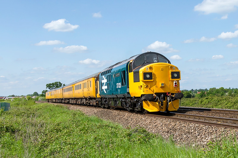 26th May 2016:  Cruising past the White Horse Business Park in North Bradley near Trowbridge  is 37025 pushing 3Z14 back from Weymouth to Bristol High Level Siding  via Chippenham
