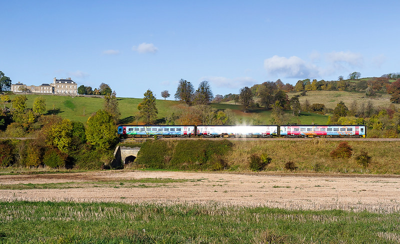 5th Nov 2016:  158798 'Springboard  Supporting Children in North Somerset with additional needs'  catching the light  as it runs beneath Kelsdon Park as it works 1F23 the 10.23 Portsmouth Harbour to Cardiff. Taken a fraction late as the glint back into the viewfinder caused me to miss a beat.