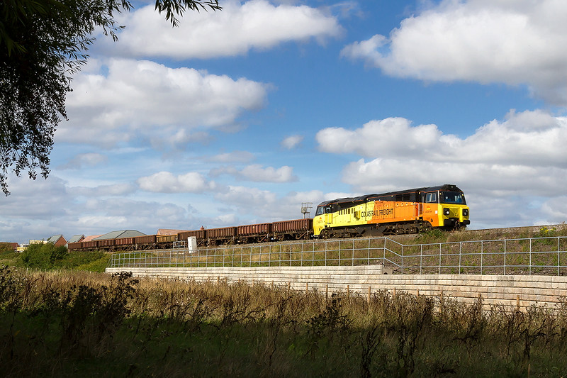11th Sep 2016:  Powering through Drynham on the edge of Trowbridge is 70805 heading 6C24 from Standish Junction to Westbury.  A part of a house roof has been cloned from the shot